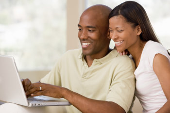 Couple smiling while using laptop